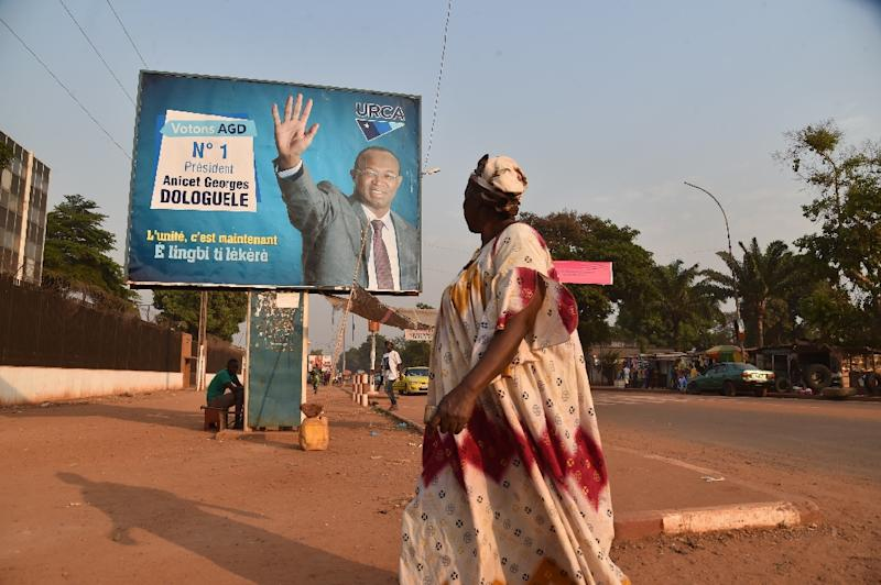 A woman walks past an electoral poster of Central African presidential candidate Anicet Georges Dologuele in the streets of the capital Bangui on December 23, 2015 (AFP Photo/Issouf Sanogo)