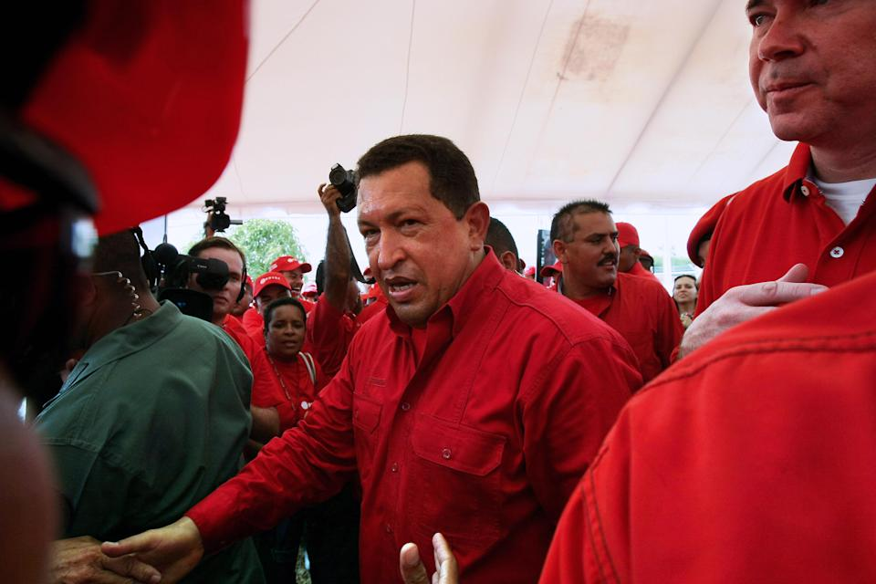Venezuela's President Hugo Chavez (C) shakes hands with the Venezuelan Petroleum company (PDVSA) employees next to Venezuelan Minister of Energy and Petroleum Rafael Ramirez (R) in Cumana, 400 km east of Caracas on October 19, 2008. Venezuela will propose a cut in the production at the OPEC' s meeting Friday and considers, that with a barrel of 80 dollars, none of its projects will be compromised, Chavez assured. AFP PHOTO / THOMAS COEX (Photo credit should read THOMAS COEX/AFP via Getty Images)