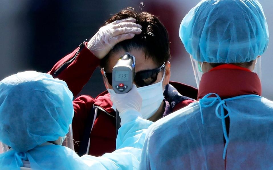 An official measures the temperature of the foreign passengers disembarking from the quarantined Diamond Princess cruise ship - AP