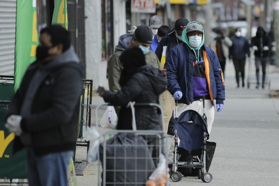 Patrons wait in line for a supermarket Thursday, April 2, 2020, in the Corona section of the Queens borough of New York. Data released by city health officials show that residents in the immigrant-rich Jackson Heights, Elmhurst and Corona sections of Queens have tested positive for the coronavirus at higher rates than in wealthy, mostly white parts of Manhattan and Brooklyn. (AP Photo/Frank Franklin II)