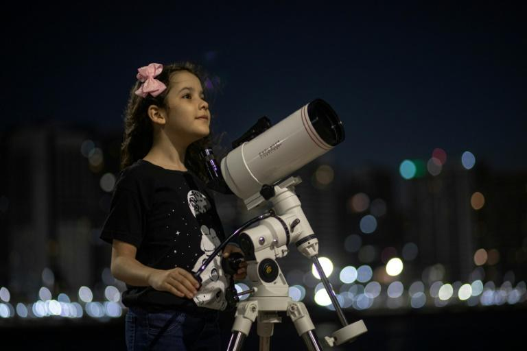Brazilian 8-year-old astronomer Nicole Oliveira poses for a picture with her telescope in Fortaleza, Brazil, on September 21, 2021 (AFP/Jarbas Oliveira)