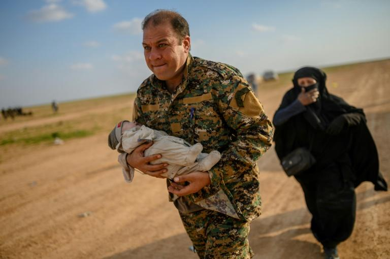 A member of the Kurdish-led Syrian Democratic Forces (SDF) carries a baby followed by a woman who fled the Islamic State (IS) group's last holdout of Baghouz, in northern Syria's Deir Ezzor province