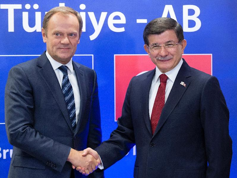 Turkish PM Ahmet Davutoglu (R) shakes hands with European Council president Donald Tusk during a bilateral meeting on sidelines of summit on relations between EU and Turkey and on migration crisis at EU headquarters in Brussels on November 29, 2015 (AFP Photo/Thierry Monasse)
