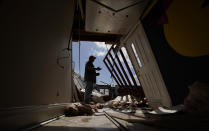 Neftali Luna surveys damages to the children's wing of the First Pentecostal Church caused by Hurricane Laura, Thursday, Aug. 27, 2020, in Orange, Texas. (AP Photo/Eric Gay)