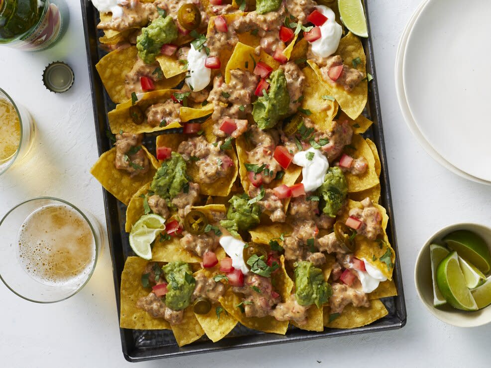 """<p>This platter of goodness represents the lowest-effort end of the homemade nachos spectrum. That said, """"low-effort""""—by no stretch of the imagination—means a low YUM-factor here. Although this game day-perfect platter of beefy, cheesy nachos comes together quickly and relies largely on store-bought shortcuts, it delivers the classic meld of flavors and textures that you want from everyone's favorite appetizer. For this nachos recipe, we combine the meat and nacho cheese elements to create a Ro*Tel Dip-inspired, beefy cheese sauce. This guarantees an even distribution of the hearty toppings and keeps you from having to crank up the oven. However, if you prefer melted, shredded cheese over a nacho cheese sauce, simply cook your ground beef in a skillet on the stovetop, drain, and distribute over the nachos on a sheet pan. Then, top the platter with shredded cheese and pop it under the broiler until melty and glorious (no Ro*Tel required).</p> <p><a href=""""https://www.myrecipes.com/recipe/quick-easy-nachos"""">Quick and Easy Nachos Recipe</a></p>"""