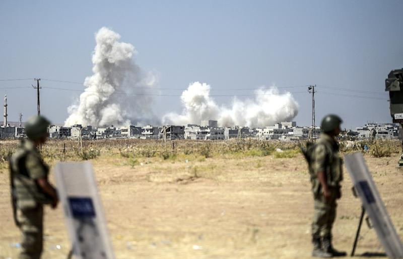 Turkish soldiers stand guard as smoke rises from the Syrian town of Kobane, also known as Ain al-Arab, on June 27, 2015