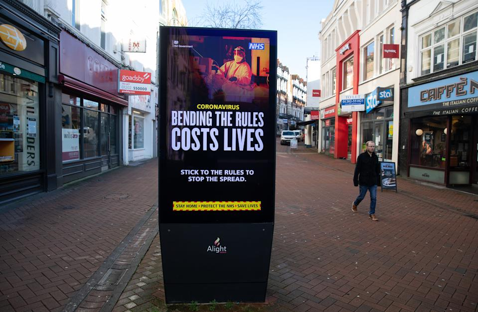 A person passes a 'Bending the rules costs lives' government coronavirus sign on Old Christchurch road in Bournemouth, during England's third national lockdown to curb the spread of coronavirus. Picture date: Friday January 22, 2021.