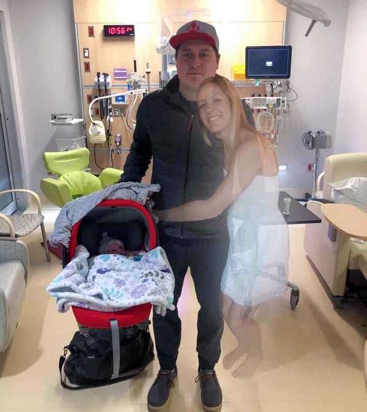 Picture of widow, Scott Jenkins taking his newborn daughter, Sydney, home for the first time, after his wife Aly Jenkins died during labor. Aly Jenkins has been added into the photo with photoshop