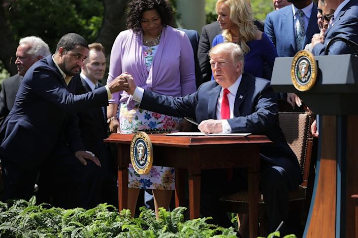 U.S. President Donald Trump shakes hands with Pastor Darrell Scott, co-founder of the New Spirit Revival Center, before Trump signs an executive order during an event in the Rose Garden to mark the National Day of Prayer at the White House May 3, 2018 in Washington, DC. (Photo by Chip Somodevilla/Getty Images)