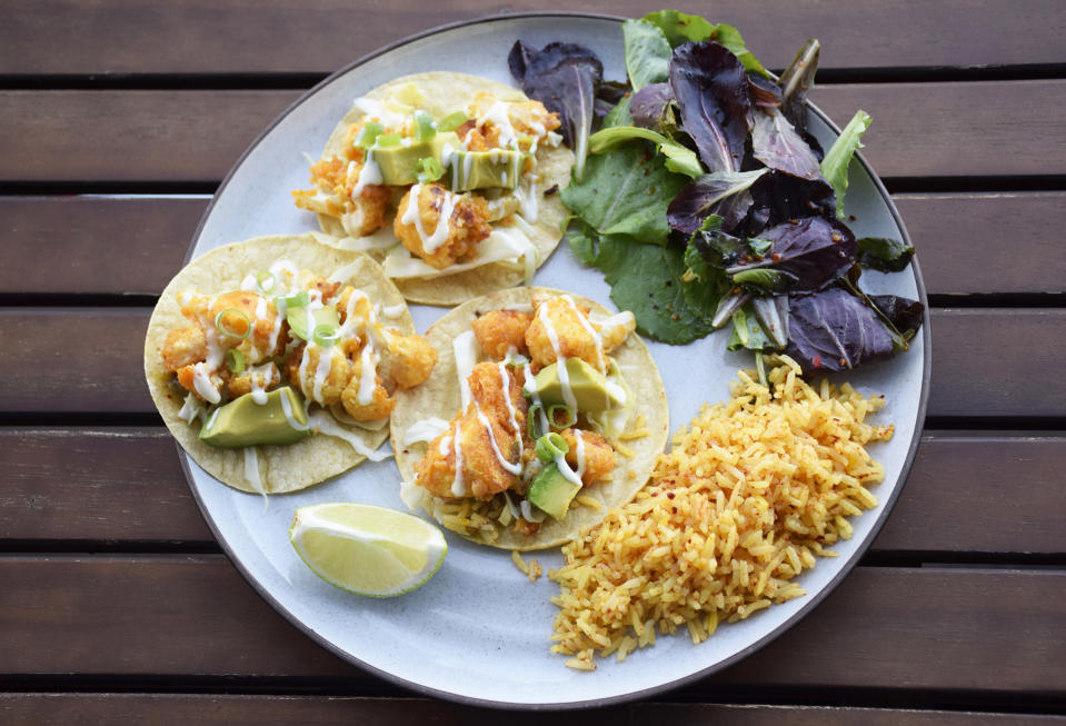 Ancho cauliflower tacos: Tacos never seem to fare well for takeout or delivery. I spiced up some battered cauliflower with an ancho chili blend over orange-marinated cabbage, served with chili rice and a salad. (Courtesy of the author)