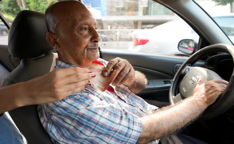 Zakaria Ghalayeeni, 76-year-old Lebanese taxi driver, receives money from a customer in Beirut