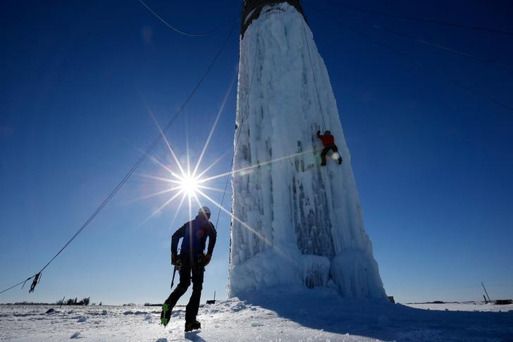 An climber ascends a silo covered in ice in Cedar Falls