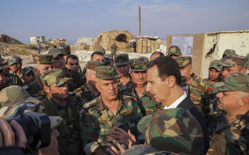 "In this photo released on the official Facebook page of the Syrian Presidency, Syrian President Bashar Assad, center right, speaks with Syrian troops during his visit to the strategic town of Habeet, in the northwestern province of Idlib, Syria, Tuesday, Oct. 22, 2019. On Tuesday, Assad called the Turkish President Recep Tayyip Erdogan a ""thief"" during his first visit to territory captured from Turkey-backed rebels in the northwestern province of Idlib. (Facebook page of the Syrian Presidency via AP)"
