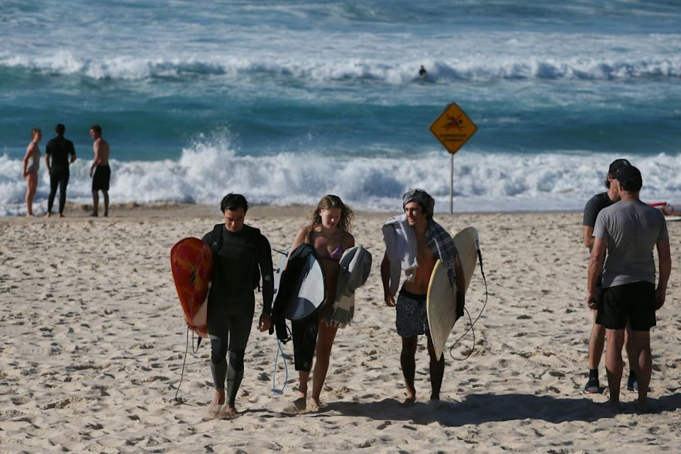 Surfers make their way up the beach after an early morning surf at Bondi Beach in Sydney, Australia.