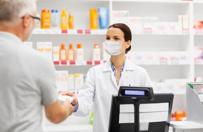 Man buying something from pharmacist with mask on