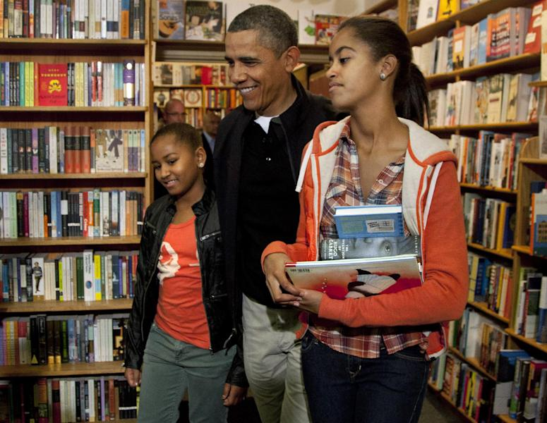 FILE - In this Nov. 26, 2011, file photo President Barack Obama visits Kramerbooks for shopping with his daughters Sasha, and Malia, right, in Washington. Obama likes to talk about his kids. What parent doesn't? But he's the president, and he brings up his daughters to explain his thinking on all sorts of combustible national issues, from the rescue of an American aid worker from Somali pirates to the touchy subject of public access to emergency contraception. (AP Photo/Carolyn Kaster)