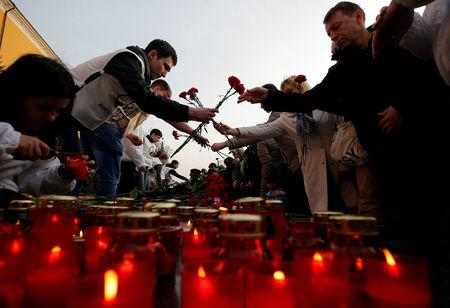 People lay flowers during a memorial to pay tribute to the victims of the St. Petersburg metro blast in central Moscow