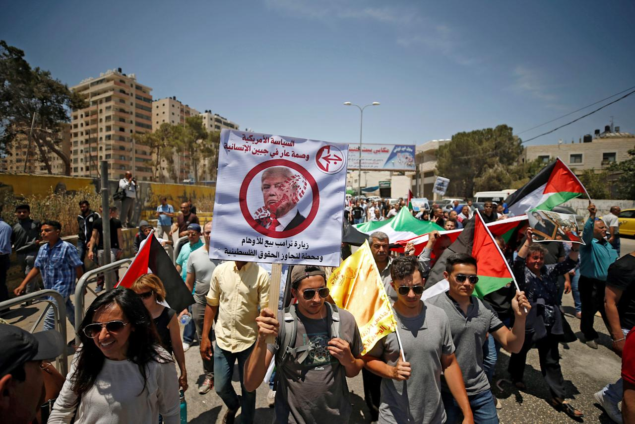 "A Palestinian demonstrator holds an anti-U.S. President Donald Trump poster during a protest in support of Palestinian prisoners on hunger strike in Israeli jails, near Qalandiya checkpoint near the West Bank city of Ramallah May 22, 2017. The poster reads, ""American policy is a stigma for humanity. Trump's visit is a delusion and stage for ignoring Palestinian rights."" REUTERS/Mohamad Torokman"