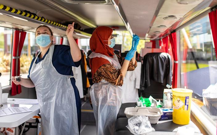 A healthcare worker prepares Covid vaccines on the Bolton Covid Vaccination bus in the Rumworth area of Bolton - James Speakman/Mercury Press