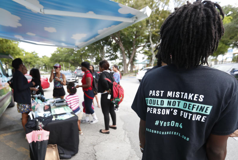 """FILE - In this Oct. 22, 2018 file photo, people gather around the Ben & Jerry's """"Yes on 4"""" truck as they learn about Amendment 4 and eat free ice cream at Charles Hadley Park in Miami. With a single vote Tuesday, Nov. 6, Florida added 1.4 million possible voters to the rolls when it passed Amendment 4, which said that most felons will automatically have their voting rights restored when they complete their sentences and probation. (AP Photo/Wilfredo Lee, File)"""