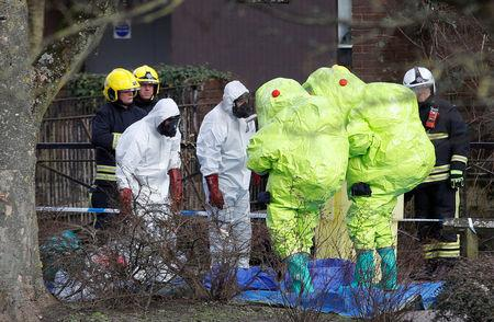 Officials in protective suits check their equipment before repositioning the forensic tent, covering the bench where Sergei Skripal and his daughter Yulia were found, in the centre of Salisbury, Britain, March 8, 2018. REUTERS/Peter Nicholls