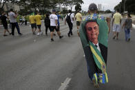 A demonstrator, wearing a cape emblazoned with an image of President Jair Bolsonaro, walks with others to the National Congress, as part of a caravan backing Bolsonaro's anti-coronavirus-lockdown stance, marking May Day, or International Workers' Day, in Brasilia, Brazil, Saturday, May 1, 2021. (AP Photo/Eraldo Peres)