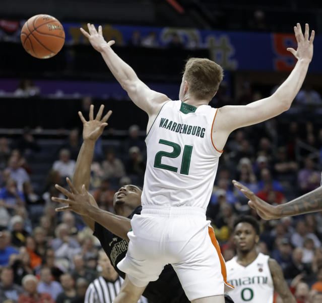 Wake Forest's Brandon Childress, bottom, tries to shoot against Miami's Sam Waardenburg (21) during the first half of an NCAA college basketball game in the Atlantic Coast Conference tournament in Charlotte, N.C., Tuesday, March 12, 2019. (AP Photo/Nell Redmond)