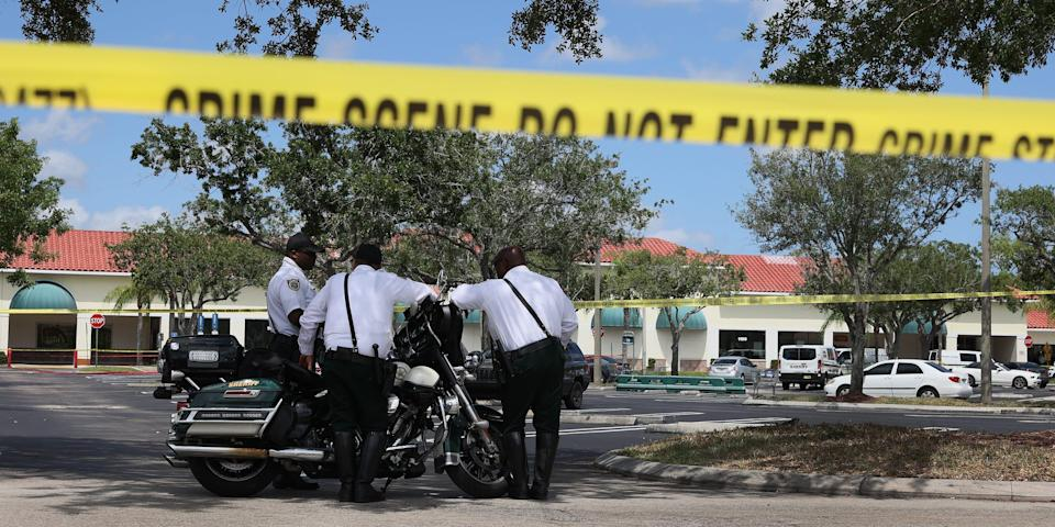 A piece of crime tape in front of a Florida Publix where officers stand outside.