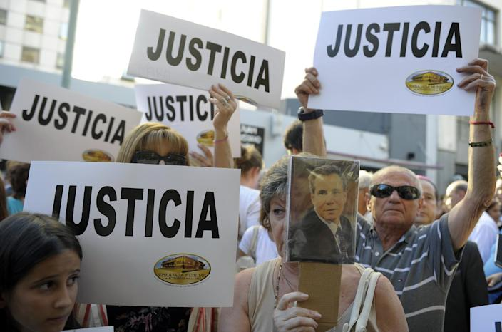 """People hold signs that read """"Justice"""" during a rally in front of the AMIA headquarters in Buenos Aires on January 21, 2015, to protest the death of Argentine public prosecutor Alberto Nisman (AFP Photo/Alejandro Pagni)"""