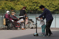 A woman plays with a child near elderly people on wheelchairs sunbathing on a compound of a commercial office building in Beijing on Monday, May 10, 2021. China's population growth is falling closer to zero as fewer couples have children, the government announced Tuesday, May 11, 2021, adding to strains on an aging society with a shrinking workforce. (AP Photo/Andy Wong)