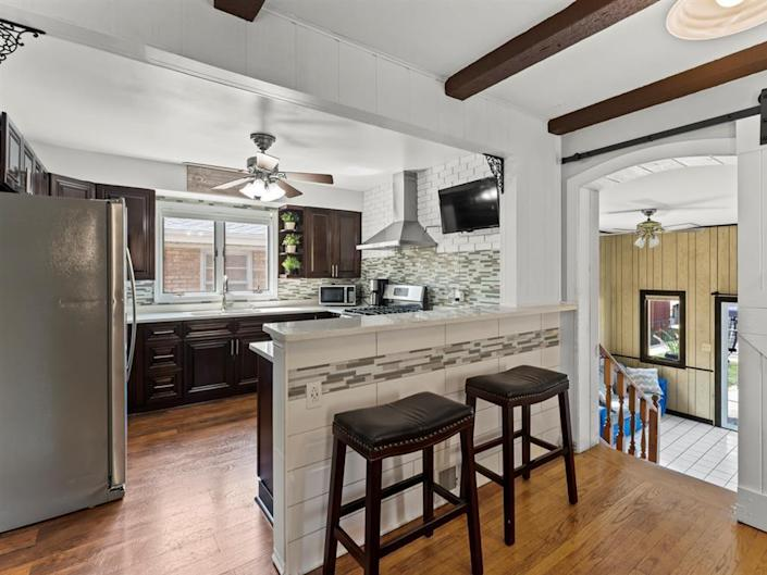 the kitchen with stools, stainless steel appliances, and wood beams in house for sale near chicago