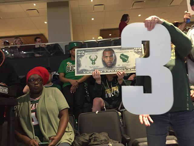 The Clutch Crew comes prepared with signs, big heads and even a $22 bill with Khris Middleton's face on it. (Yahoo Sports)
