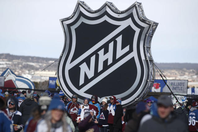 Fans pose below the NHL league logo at a display outside Falcon Stadium before an NHL Stadium Series outdoor hockey game between the Los Angeles Kings and Colorado Avalanche, Saturday, Feb. 15, 2020, at Air Force Academy, Colo. (AP Photo/David Zalubowski)