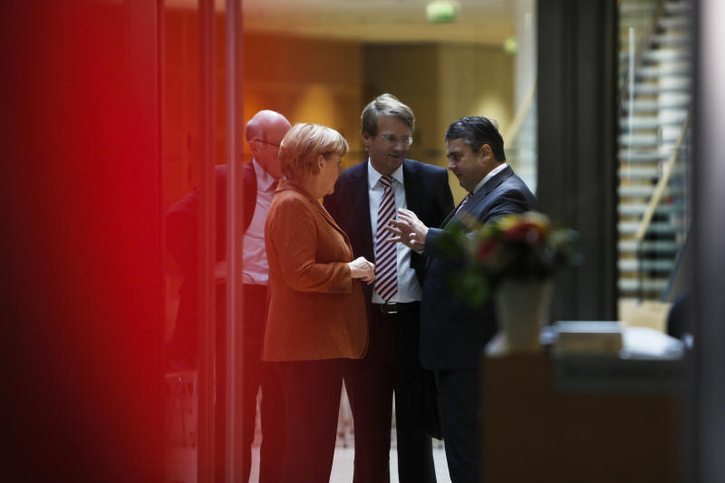 Social Democratic Party, SPD, chairman Sigmar Gabriel, right, welcomes Angela Merkel, German Chancellor and chairwoman of the Christian Democratic Union, CDU, left, and the Chief of Staff at the chancellery Ronald Pofalla, center, at the Social Democrat's headquarters for coalition talks in Berlin, Wednesday, Oct. 30, 2013. Following the Sept. 22 national elections Chancellor Merkel and her Christian parties' bloc are negotiating the second week on forming a coalition with the Social Democratic Party. (AP Photo/Markus Schreiber)