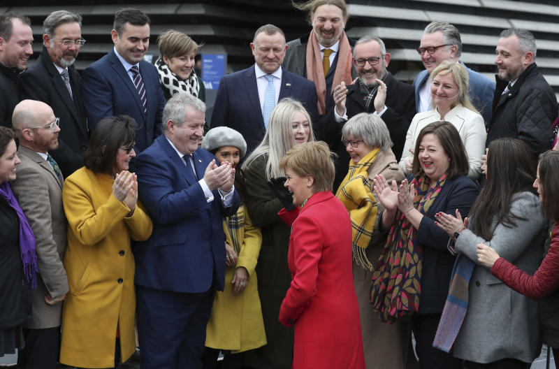 Scottish First Minister Nicola Sturgeon, centre, is greeted by newly elected candidates of Scottish National Party (SNP) during a photo opportunity as they gather outside the V&A Museum in Dundee, Scotland, Saturday Dec. 14, 2019.  Sturgeon delivered a landslide election victory for the SNP, with a campaign focused on demands for a second referendum on Scottish independence, but Prime MinisterBoris Johnson has flatly rebuffed the idea of another vote. (Andrew Milligan/PA via AP)