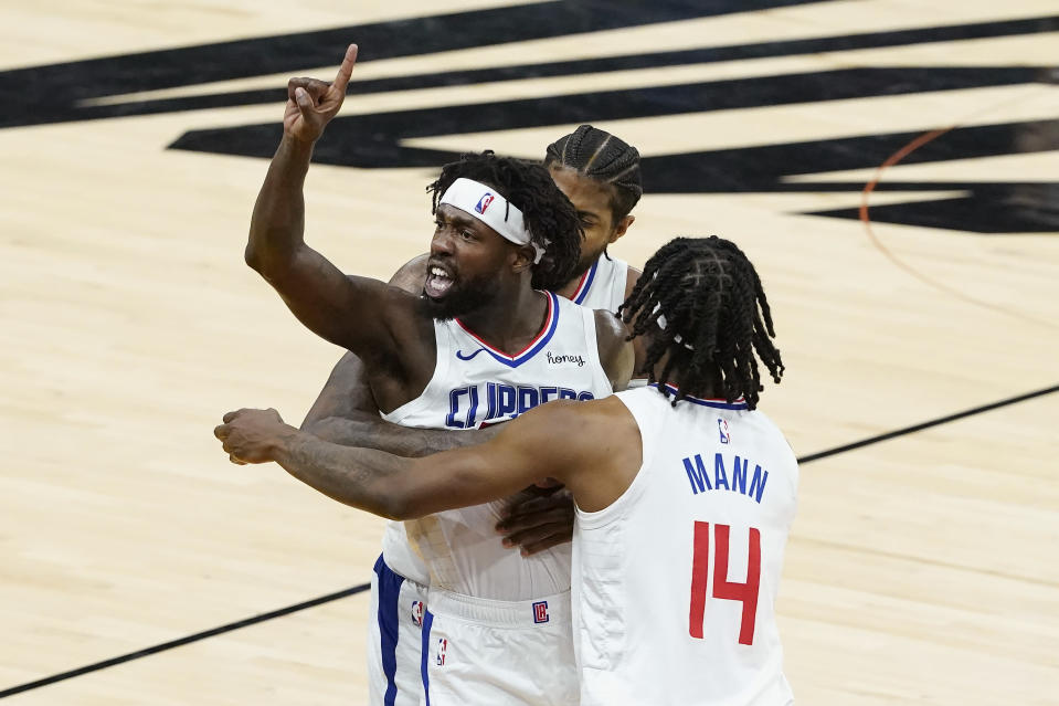 Los Angeles Clippers guard Patrick Beverley, middle, gestures toward fans while celebrating with Paul George, rear, and Terance Mann (14) during the second half of Game 2 of the NBA basketball Western Conference Finals against the Phoenix Suns, Tuesday, June 22, 2021, in Phoenix. (AP Photo/Matt York)