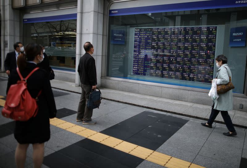 People wearing protective face masks look at a stock quotation board outside a brokerage in Tokyo