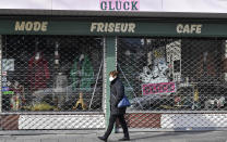 A woman with a face mask passes a closed combined cafe, barber and fashion shop named Glueck (luck) in Duisburg, Germany, Monday, Jan. 25, 2021. (AP Photo/Martin Meissner)