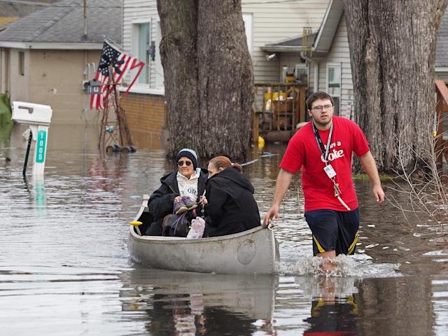 <p>Garry Clark, 15, uses a canoe to take his grandmother Jeanne Kendall and June Wedl from their flooded home Thursday, Feb. 22, 2018 in Comstock's Lakewood neighborhood. Severe and record-breaking flooding is predicted for the Kalamazoo River at Comstock, the National Weather Service Grand Rapids said Thursday. (Photo: Mark Bugnaski/Kalamazoo Gazette-MLive Media Group via AP) </p>
