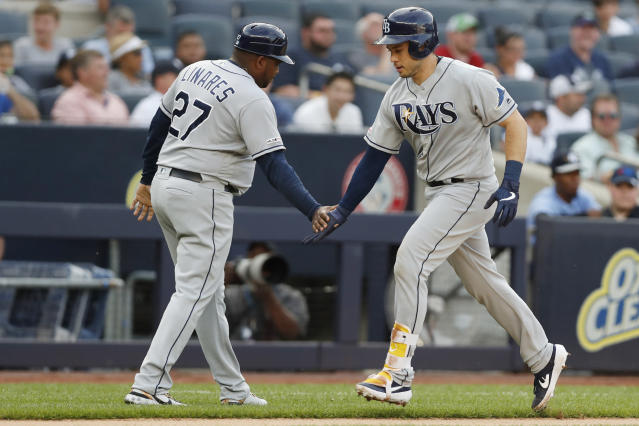 Tampa Bay Rays' third base coach Rodney Linares (27) slaps hands with Travis d'Arnaud who runs the bases after hitting a solo home run during the first inning of a baseball game against the New York Yankees, Monday, July 15, 2019, in New York. (AP Photo/Kathy Willens)