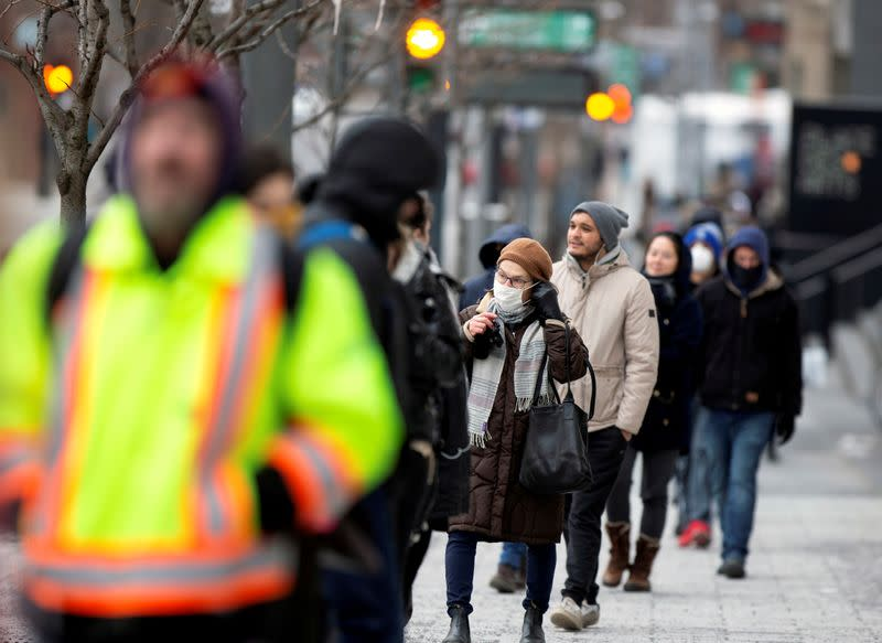 FILE PHOTO: A woman adjusts her mask while she waits in line as the city's public health unit holds a walk-in clinic testing for coronavirus disease (COVID-19) in Montreal