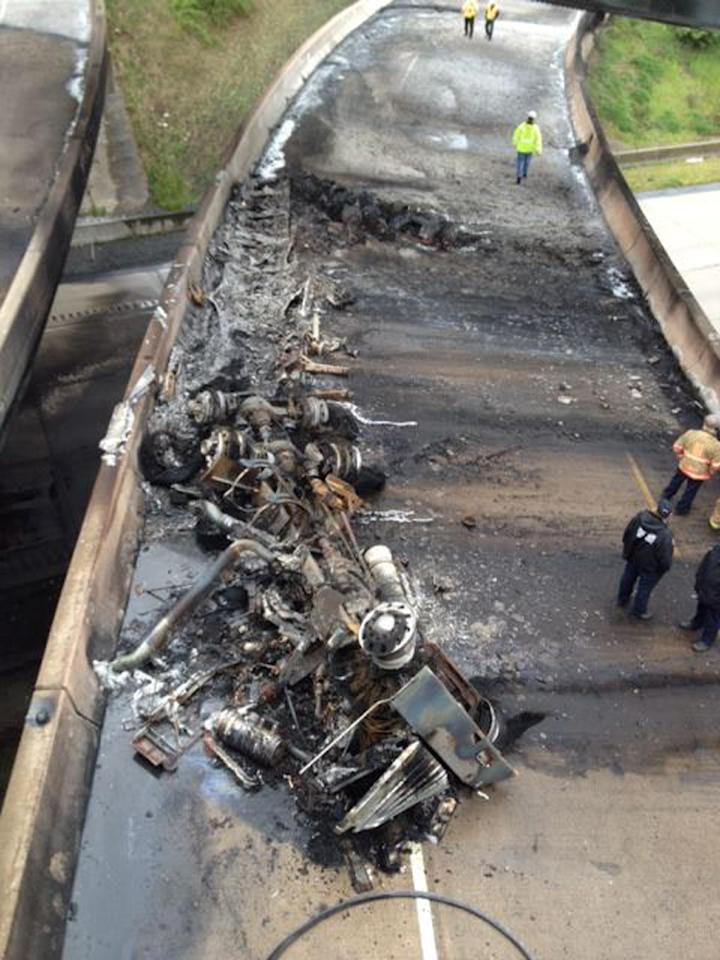 This photo provided by Andrew Huston shows what remains of a tanker truck that was loaded with diesel fuel after it overturned and burned along Interstate 81, shutting down the heavily traveled artery near Harrisburg, Pa. on Thursday, May 9, 2013. The truck was headed northbound from Carlisle shortly after 6 a.m. when it flipped over on a ramp to Route 22-322 westbound, near the I-81 bridge over the Susquehanna River. State police said the driver, a 52-year-old from Dover, Pa., was treated at a hospital for minor injuries. (AP Photo/Andrew Huston)