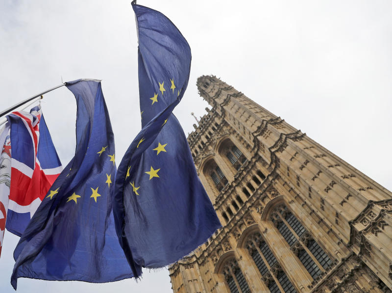 Flags of Anti Brexit protestors fly in front of parliament in London, Wednesday, Oct. 23, 2019. Britain's government is waiting for the EU's response to its request for an extension to the Brexit deadline. (AP Photo/Frank Augstein)