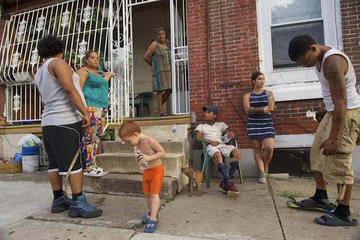 People congregate on a rowhouse stoop in the historically Puerto Rican Hunting Park neighbourhood in North Philadelphia (Mark Makela for The Washington Post)