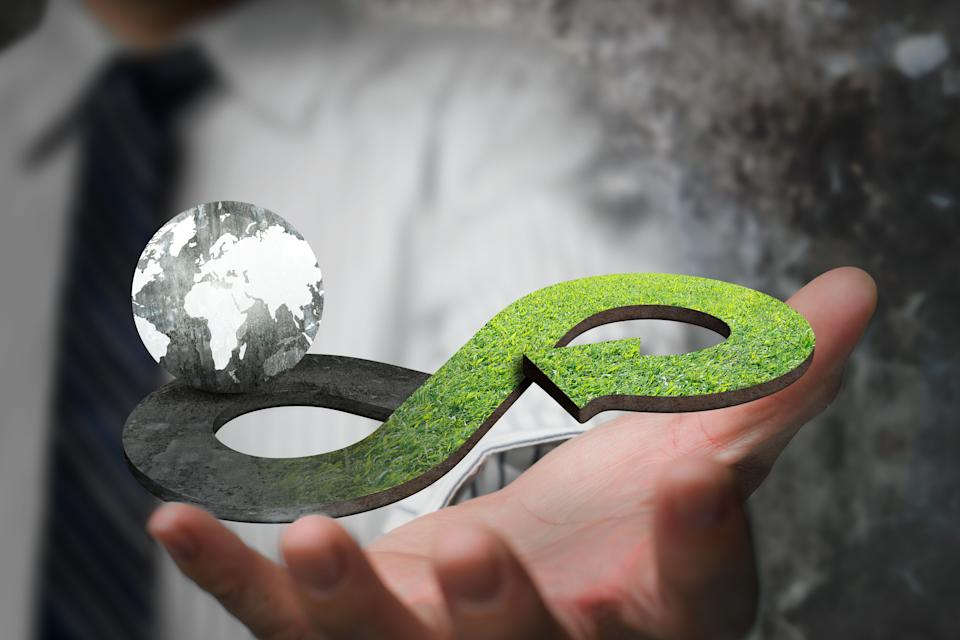 Green circular economy concept. Hand showing arrow infinity symbol with grass texture and globe. (Photo: BsWei via Getty Images)