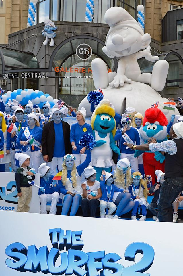 BRUSSELS, BELGIUM - JUNE 22: Smurf Ambassadors pose for a group photo below a Smurf sculpture in front of the Brussels Central railway station as part as Global Smurfs Day celebrations on June 22, 2013 in Brussels, Belgium. (Photo by Pascal Le Segretain/Getty Images for Sony Pictures Entertainment)