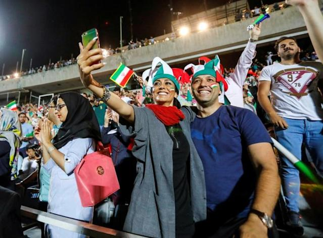 """An Iranian couple pose for a """"selfie"""" while cheering for their national fooball team during a screening of a Russia 2018 World Cup Group B football match between Iran and Spain at Azadi stadium in Tehran on June 20, 2018 (AFP Photo/STRINGER)"""