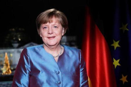 German Chancellor Angela Merkel poses for photographs after the television recording of her annual New Year's speech at the Chancellery in Berlin