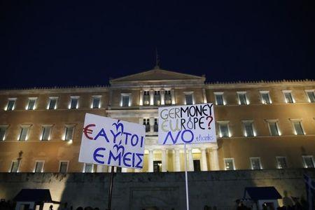 Protesters hold banners in front of the parliament building during an anti-austerity rally in Athens, Greece, June 29, 2015. REUTERS/Alkis Konstantinidis