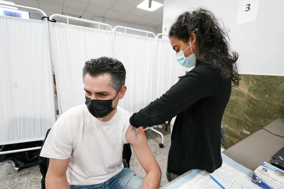 A Northwell Health registered nurse inoculates mosque member Albert Capa with the Johnson & Johnson COVID-19 vaccine at a pop up vaccinations site the Albanian Islamic Cultural Center, Thursday, April 8, 2021, in the Staten Island borough of New York. Ahead of Ramadan, Islamic leaders are using social media, virtual town halls and face-to-face discussions to spread the word that it's acceptable for Muslims to be vaccinated during daily fasting that happens during the holy month. (AP Photo/Mary Altaffer)